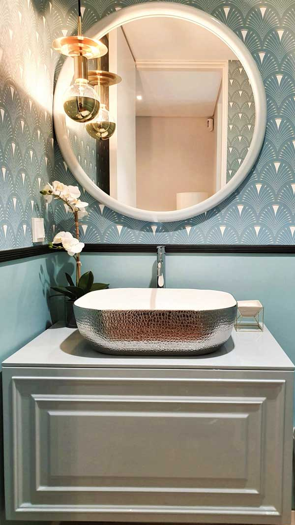 silver-washbowl-with-rounded-mirror-and-golden-wall-lamp-and-wallpaper-in-bathroom-design-by-helder-calca
