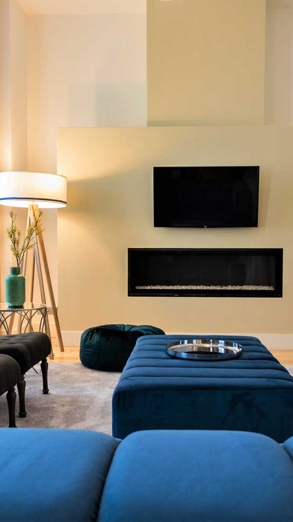 living-room-design-by-helder-calca-combining-neutral-colors-with-blue-and-green-with-a-fireplace-and-a-carpet-and-a-glass-table-and-a-floor-lamp